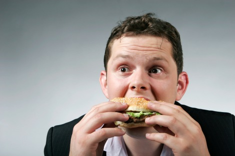 Hungry businessman enjoying a big burger